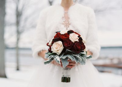 Bride in white fur with red blush and dusty miller bouquet | The Ivy Lea Club | AMBPhoto