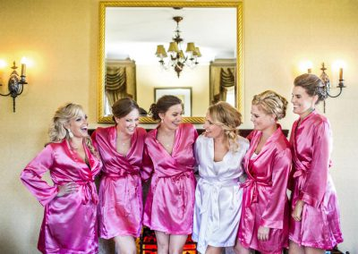 Bridesmaids in pink satin robes bride in white satin | Fairmont Chateau Laurier | Union Eleven Photographers